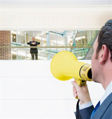 Businessman with bullhorn yelling up at boss Stock Photo - Premium Royalty-Free, Code: 635-03641979