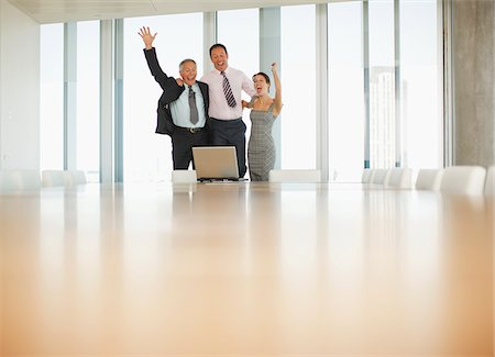 Excited business people celebrating in front of laptop in conference room Stock Photo - Premium Royalty-Free, Code: 635-03641972