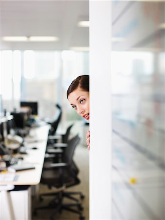 Curious businesswoman peering around corner in office Stock Photo - Premium Royalty-Free, Code: 635-03641996