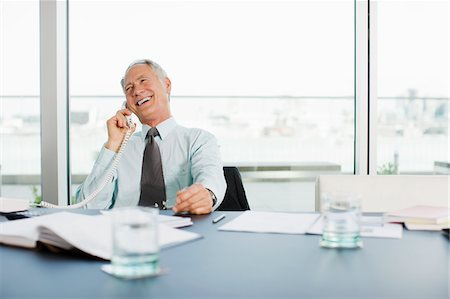 Smiling businessman talking on telephone in office Stock Photo - Premium Royalty-Free, Code: 635-03641990