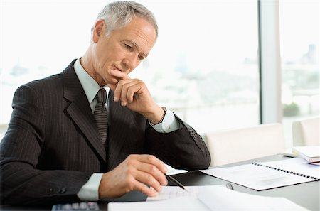 Focused businessman reading paperwork in office Stock Photo - Premium Royalty-Free, Code: 635-03641991