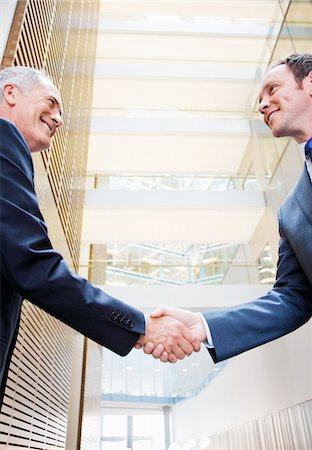 Smiling businessmen shaking hands in lobby Stock Photo - Premium Royalty-Free, Code: 635-03642019