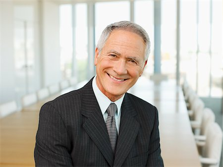Smiling businessman in empty conference room Stock Photo - Premium Royalty-Free, Code: 635-03642036
