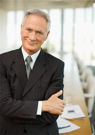 Smiling businessman with arms crossed in empty conference room Stock Photo - Premium Royalty-Free, Code: 635-03642037