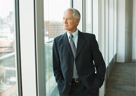 Smiling businessman looking out office window Stock Photo - Premium Royalty-Free, Code: 635-03642030