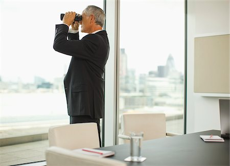 Businessman with binoculars looking out office window Stock Photo - Premium Royalty-Free, Code: 635-03642031