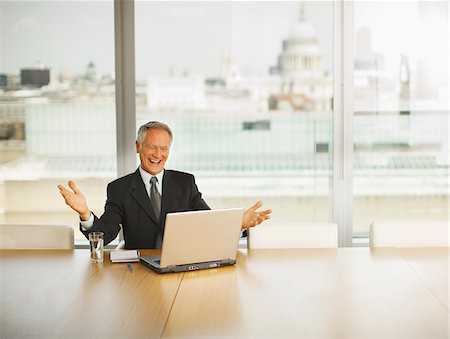 Happy businessman gesturing and looking at computer in conference room Stock Photo - Premium Royalty-Free, Code: 635-03642032
