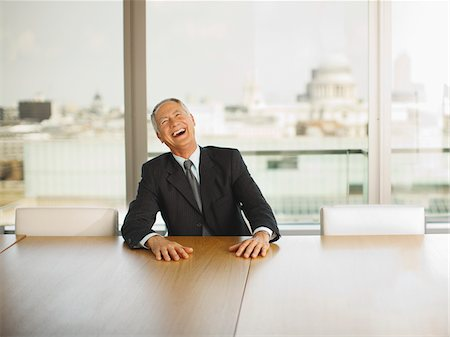 Businessman laughing in conference room Stock Photo - Premium Royalty-Free, Code: 635-03642033