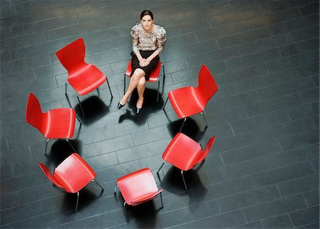 red chair - Businesswoman sitting alone in circle of chairs Stock Photo - Premium Royalty-Free, Code: 635-03642040