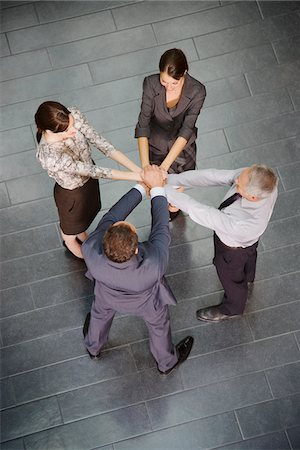 Business people standing in circle with hands stacked Stock Photo - Premium Royalty-Free, Code: 635-03642041