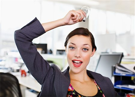 results - Confident businesswoman holding light bulb overhead in office Stock Photo - Premium Royalty-Free, Code: 635-03642054