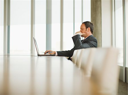 dubious - Businessman working on laptop in empty conference room Stock Photo - Premium Royalty-Free, Code: 635-03642059