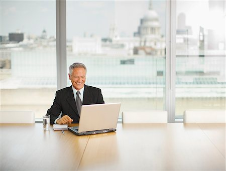 Smiling businessman using laptop in conference room Stock Photo - Premium Royalty-Free, Code: 635-03642064