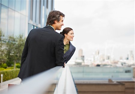 funny looking people - Smiling business people leaning on railing outside office building Stock Photo - Premium Royalty-Free, Code: 635-03642074
