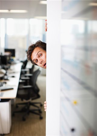 Curious businessman peering around corner in office Stock Photo - Premium Royalty-Free, Code: 635-03642077