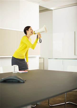 Businesswoman shouting in bullhorn in conference room Stock Photo - Premium Royalty-Free, Code: 635-03642073