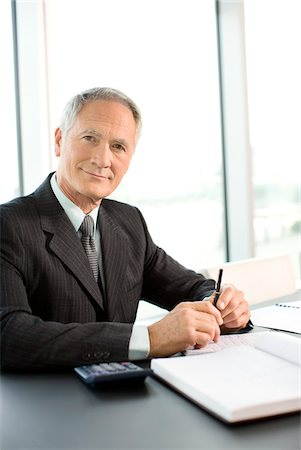 Smiling businessman sitting at desk in office Stock Photo - Premium Royalty-Free, Code: 635-03642085