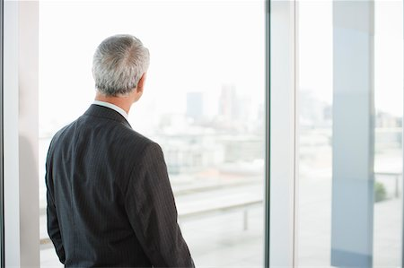 Businessman looking out office window Stock Photo - Premium Royalty-Free, Code: 635-03642086