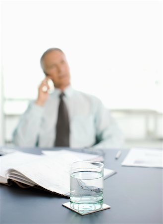 Pensive businessman sitting at desk in office Stock Photo - Premium Royalty-Free, Code: 635-03642087