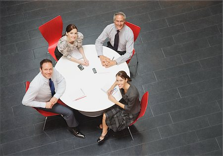 Smiling business people sitting at round table and having a meeting Stock Photo - Premium Royalty-Free, Code: 635-03642098