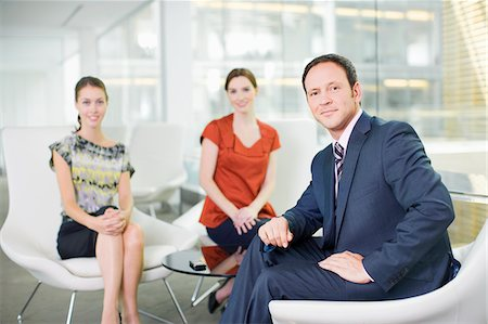 Smiling business people sitting in lobby Stock Photo - Premium Royalty-Free, Code: 635-03642093