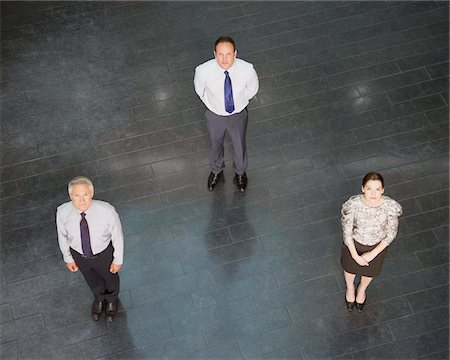 Business people standing in triangle Stock Photo - Premium Royalty-Free, Code: 635-03642101