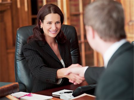 Smiling lawyers shaking hands in office Stock Photo - Premium Royalty-Free, Code: 635-03642128