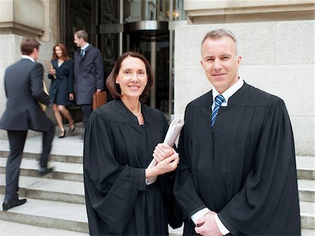 Smiling judges in robes standing outside courthouse Stock Photo - Premium Royalty-Free, Code: 635-03642133