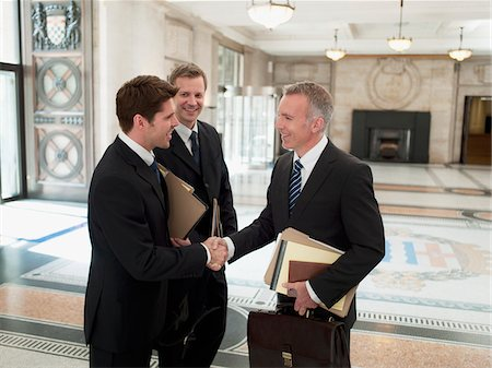 Smiling lawyers with files shaking hands in lobby Stock Photo - Premium Royalty-Free, Code: 635-03642142