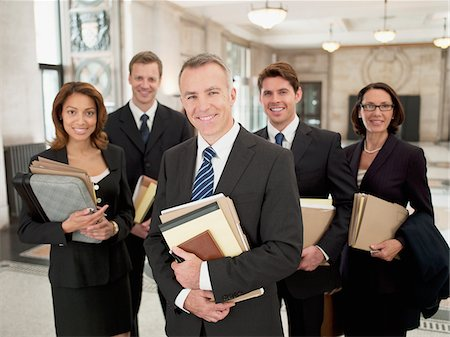 five people - Smiling lawyers holding files in lobby Stock Photo - Premium Royalty-Free, Code: 635-03642143
