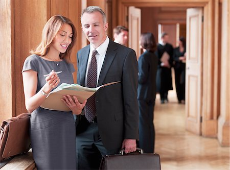 Lawyers reviewing case file in corridor Stock Photo - Premium Royalty-Free, Code: 635-03642155