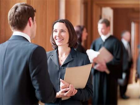 Lawyers talking in corridor Stock Photo - Premium Royalty-Free, Code: 635-03642157