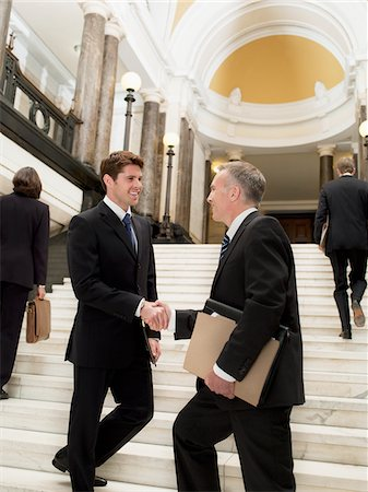 Smiling lawyers shaking hands on stairs Stock Photo - Premium Royalty-Free, Code: 635-03642153