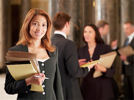 Smiling lawyer holding files in corridor Stock Photo - Premium Royalty-Free, Code: 635-03642178
