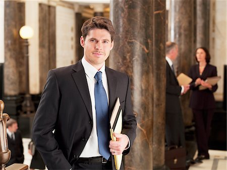 Smiling businessman leaning against pillar in corridor Stock Photo - Premium Royalty-Free, Code: 635-03642179