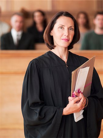 Confident judge holding file in courtroom Stock Photo - Premium Royalty-Free, Code: 635-03642185