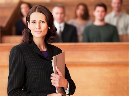 Smiling lawyer holding file in courtroom Stock Photo - Premium Royalty-Free, Code: 635-03642186