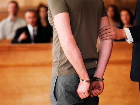 Handcuffed man standing in courtroom Stock Photo - Premium Royalty-Free, Code: 635-03642189