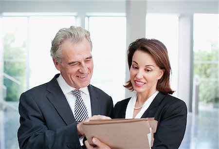 Smiling business people reviewing file in office Stock Photo - Premium Royalty-Free, Code: 635-03642182