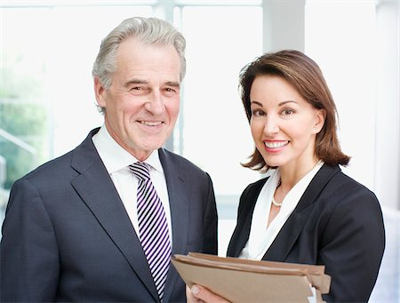 Smiling business people holding files in office Stock Photo - Premium Royalty-Free, Code: 635-03642183