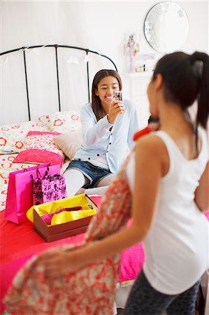 Teenage girl taking photograph of friend's dress Stock Photo - Premium Royalty-Free, Code: 635-03684977