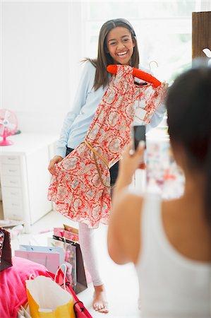 Teenage girl taking photograph of friend's dress Stock Photo - Premium Royalty-Free, Code: 635-03684978