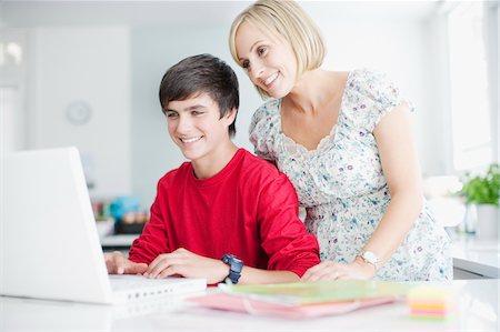 Mother watching teenage son using laptop Stock Photo - Premium Royalty-Free, Code: 635-03685003