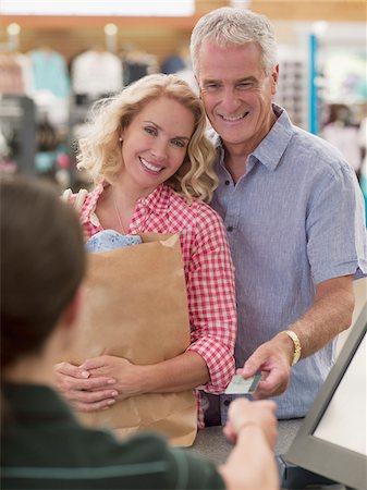 Smiling couple with shopping bag handing credit card to cashier Stock Photo - Premium Royalty-Free, Code: 635-03685046