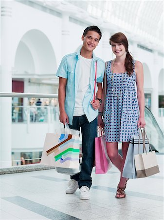 Smiling couple carrying shopping bags in mall Stock Photo - Premium Royalty-Free, Code: 635-03685069