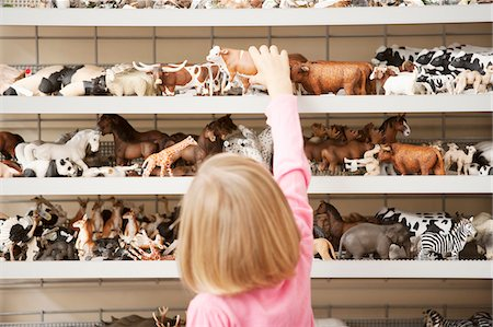 Girl reaching for plastic cow in toy store Stock Photo - Premium Royalty-Free, Code: 635-03685099