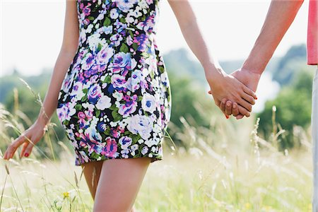 Couple holding hands and walking in field Stock Photo - Premium Royalty-Free, Code: 635-03685102