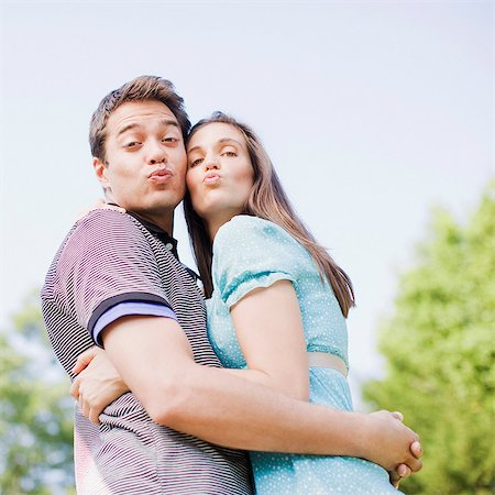 Puckering couple hugging outdoors Stock Photo - Premium Royalty-Free, Code: 635-03685118
