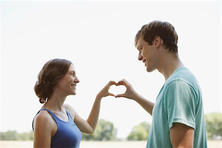 expectation - Smiling couple using hands to make heart shape Stock Photo - Premium Royalty-Free, Code: 635-03685186