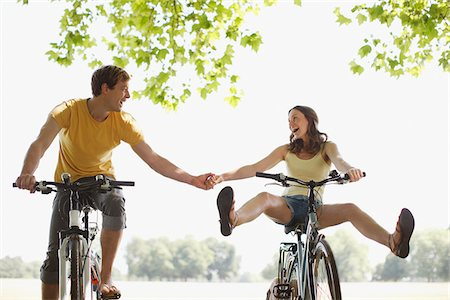 Happy couple riding bicycles and holding hands Stock Photo - Premium Royalty-Free, Code: 635-03685198